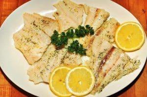 柠檬片装在盘子里的鱼类