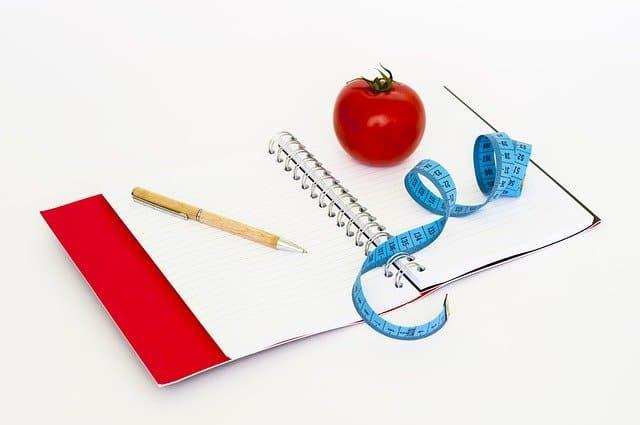 一本笔记本,一支笔,一把卷尺和一个西红柿。