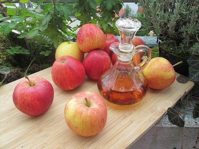 桌上的新鲜苹果和一瓶苹果醋