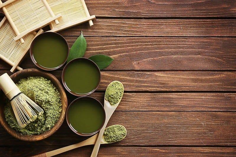 抹茶绿茶粉在沙拉碗和杯子里以液体形式存在。