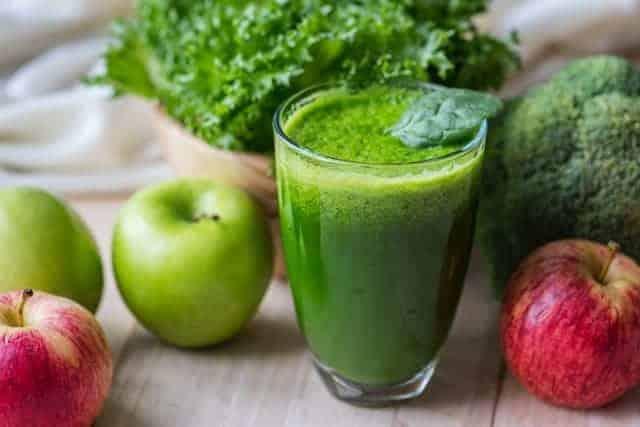 蔬菜绿色冰沙在玻璃杯和苹果