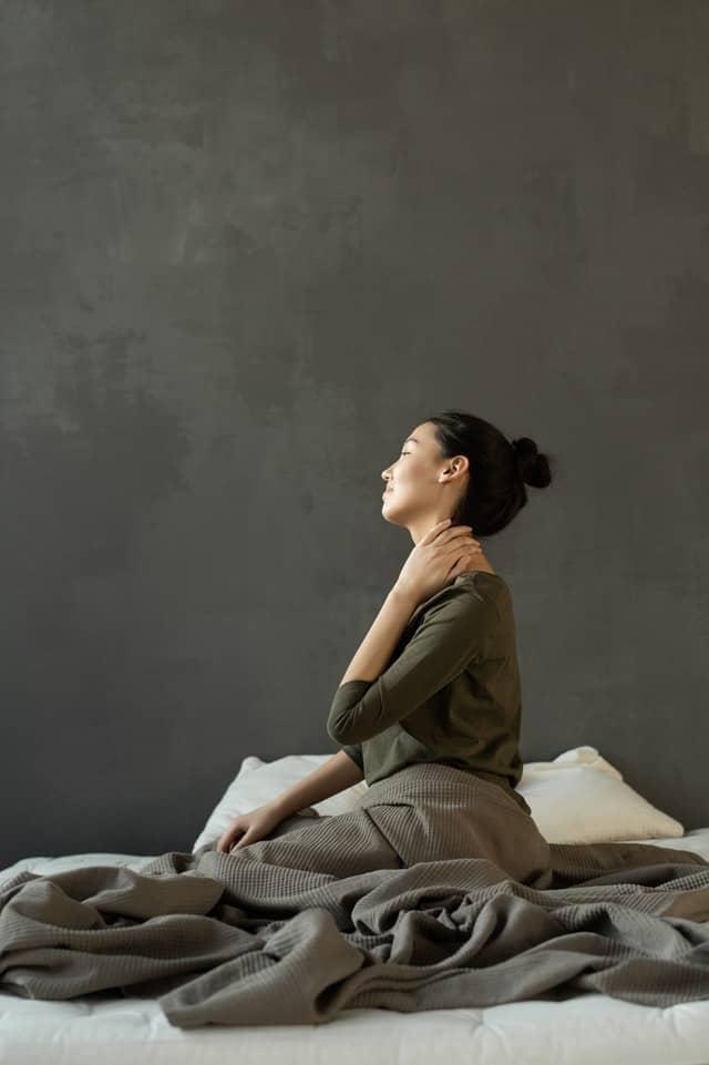 女人坐在床上,抱着她的脖子,背部疼痛。
