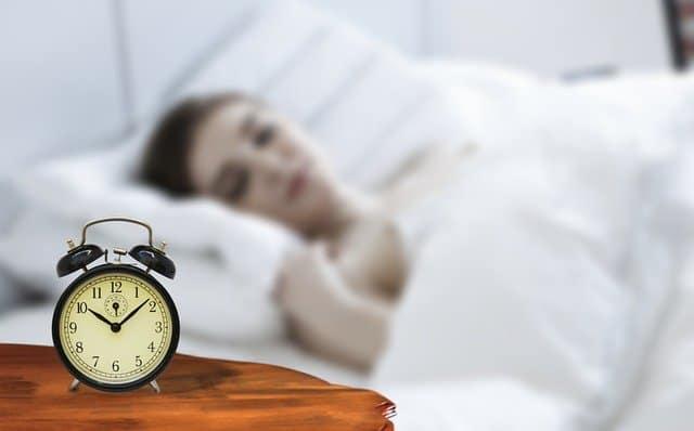女人睡觉,床头有闹钟
