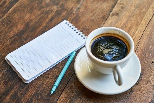 一杯咖啡,一个笔记本,一支笔。