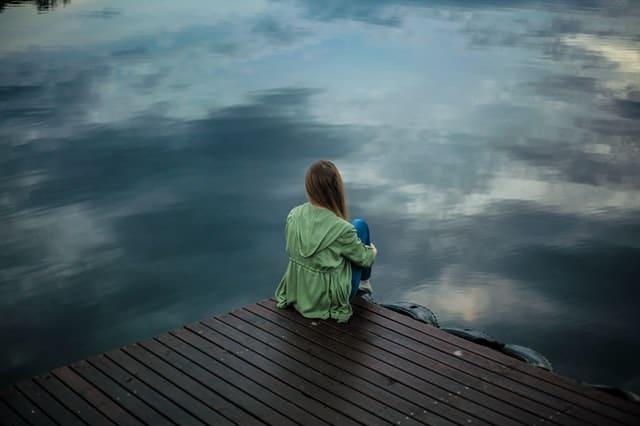 一个女人坐在码头边上,看着水面。