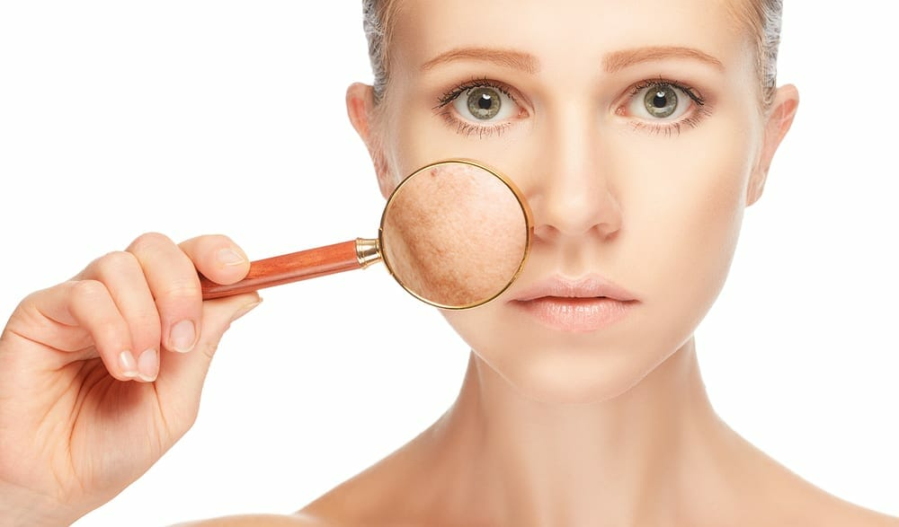 一个女人通过放大镜观察自己的肤色