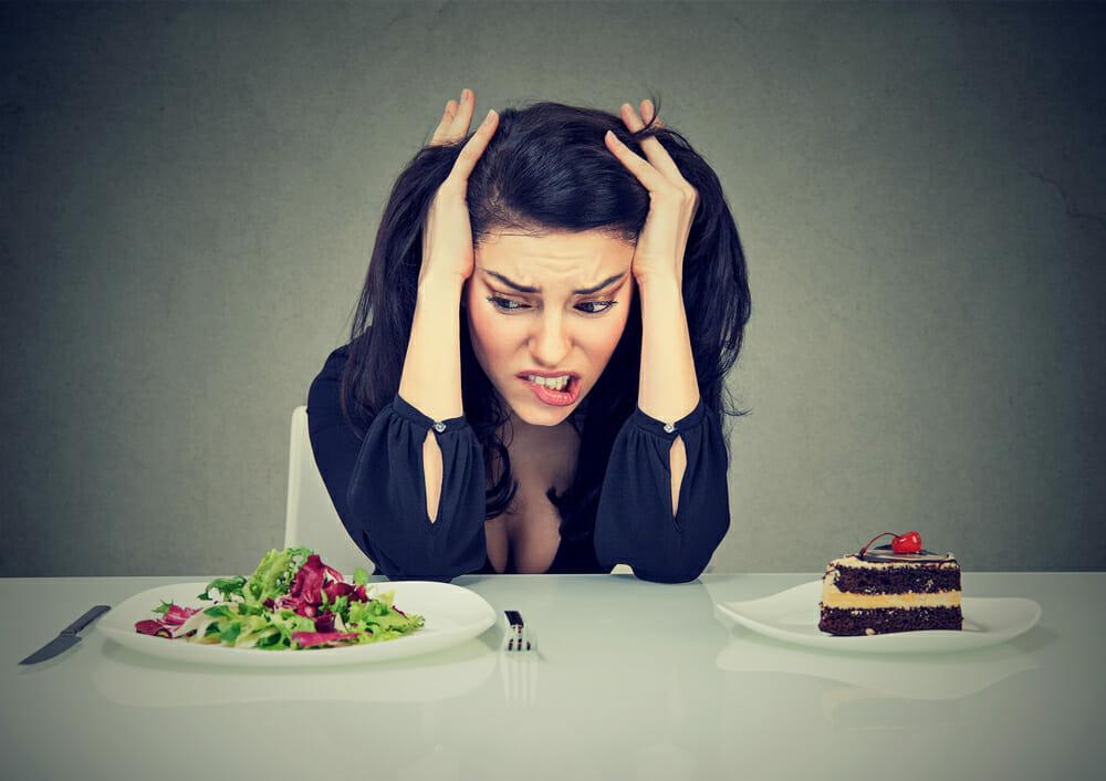 一个女人坐在桌子上,拿着一盘蛋糕和一盘沙拉