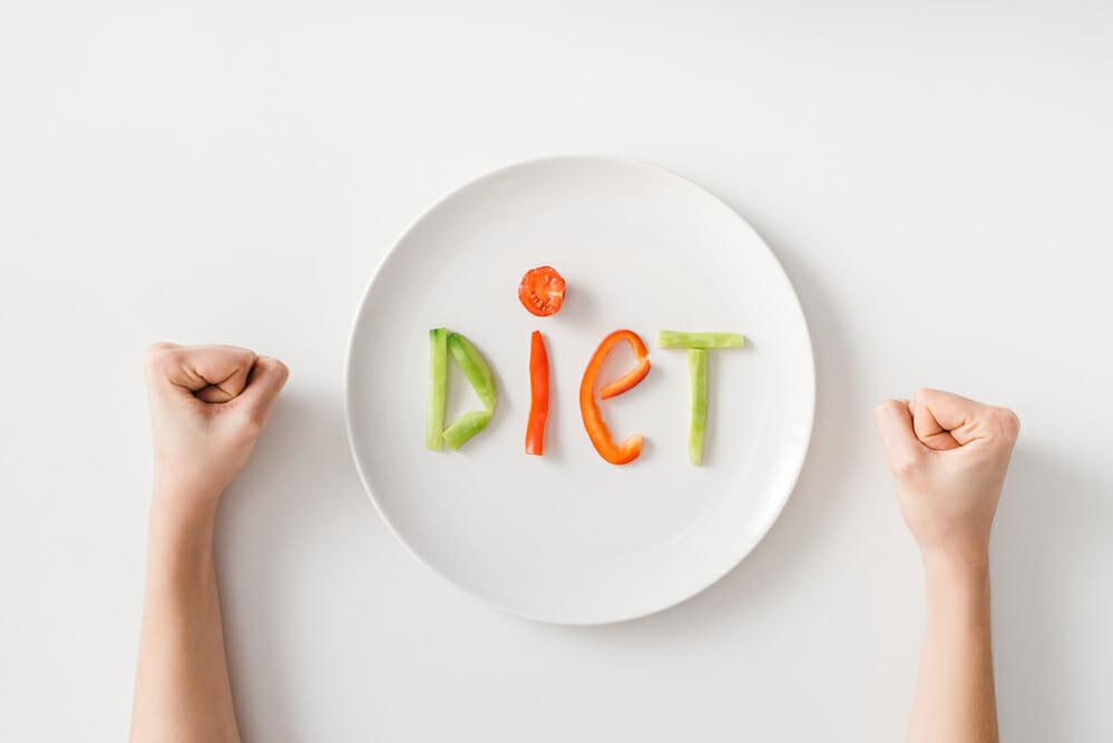 攥紧拳头,一个盘子,盘子里有几块蔬菜
