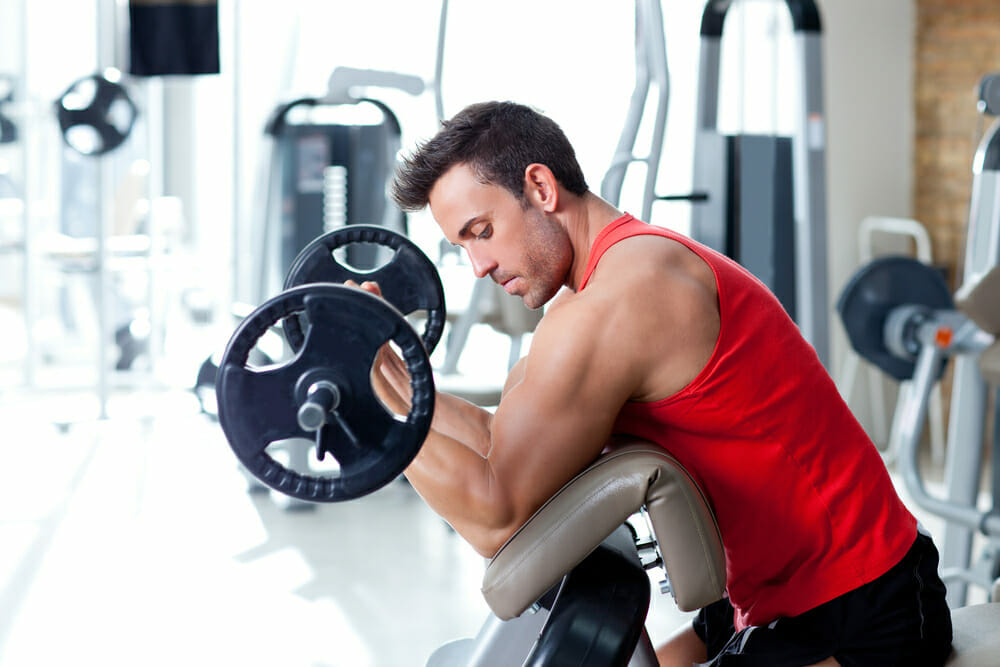 一名男子在健身房用杠铃锻炼。