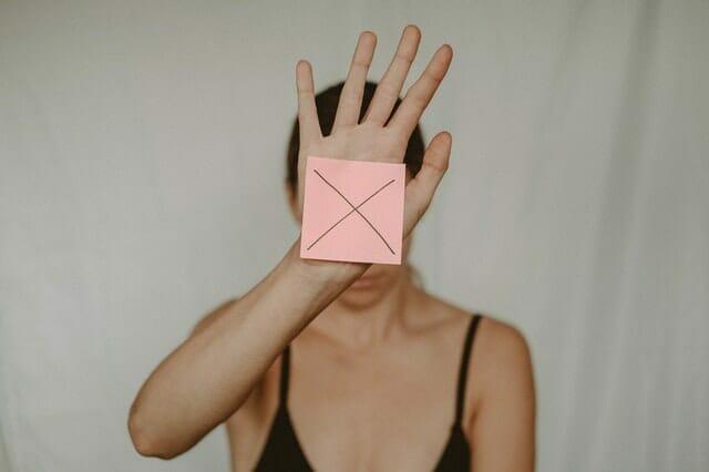 一个悲伤的女人拿着一个带X的纸盒在她面前晃来晃去